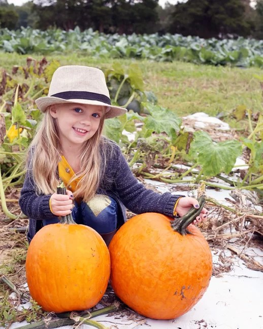 A girl with two pumpkins