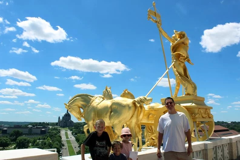 Chris and the kids on the roof in front of the golden statue.