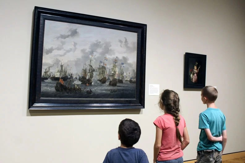 The kids looking at an oil painting of a naval battle.