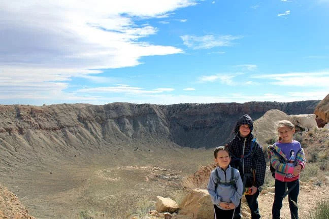 Three kids in front of a huge meteor crater.