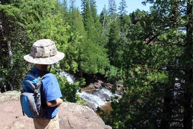 Boy with backpack looking over a cliff