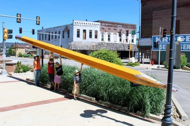 An entire family holding up a huge pencil!