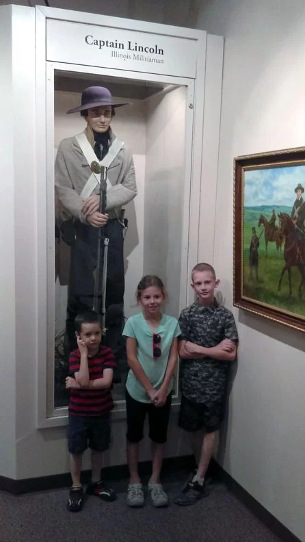 Three kids in front of a wax statue of Lincoln dressed as he did when he was a soldier in the  land of lincoln
