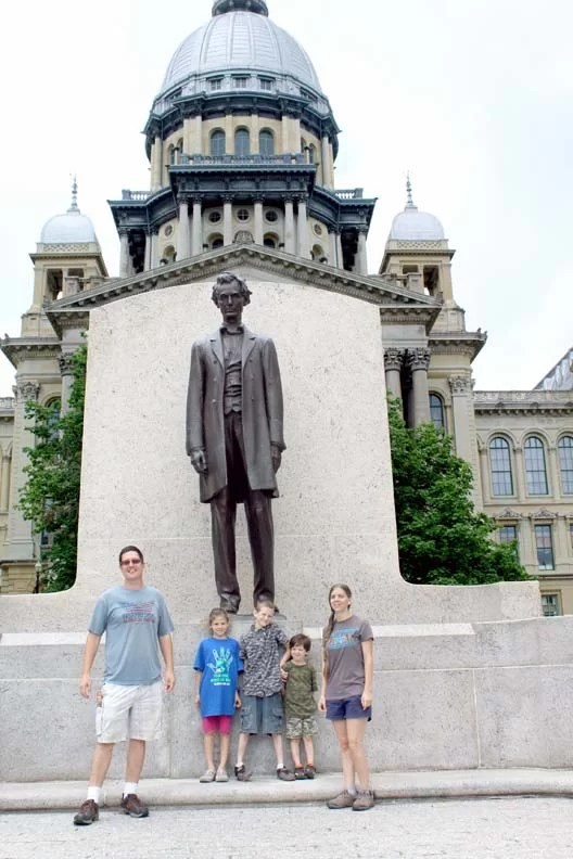 Illinois capitol building with a family posing in front of the Lincoln statue.