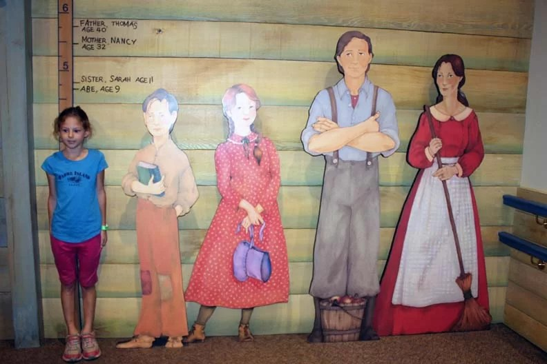 A girl next to cutouts of the Lincoln family.