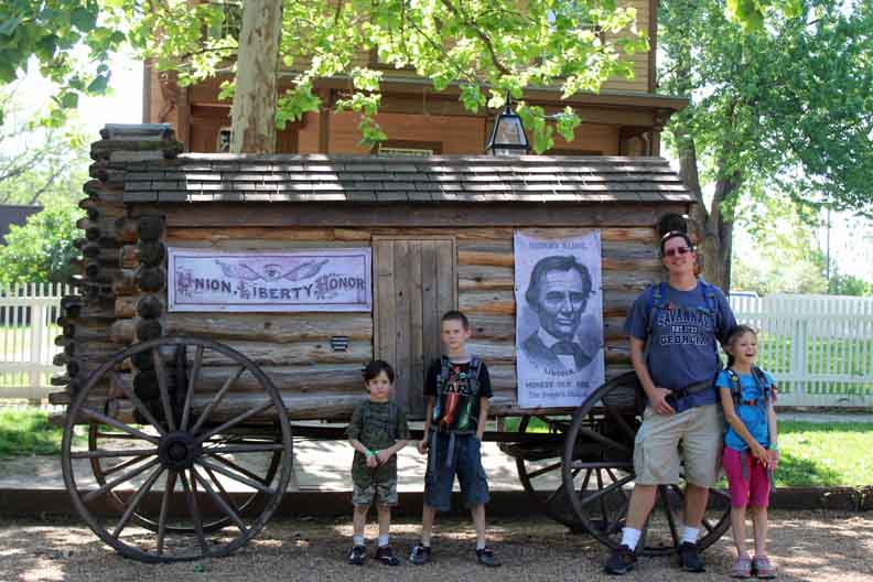 An old campaign wagon with Lincoln on it and three guys posing in the land of Lincoln.