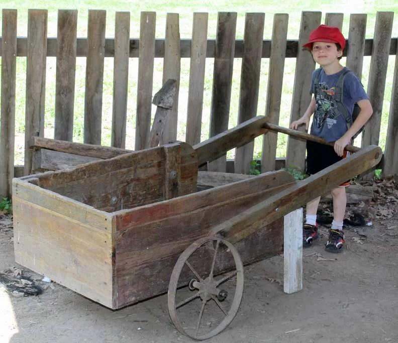 A boy holding the handle of an old wheelbarrow.