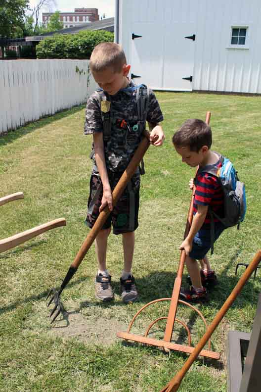 Two boys using old yard tools.