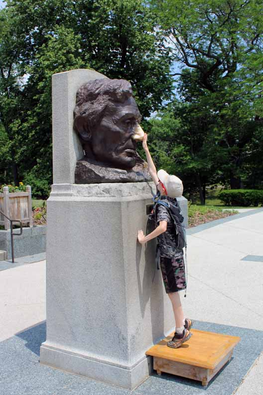 A kid rubbing the nose of Lincoln on a statue.