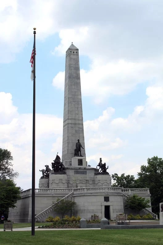 A statue of Lincoln with his tomb monument in the back ground in the land of Lincoln.