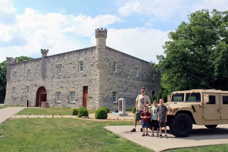 A family next to a military humvee in front of the museum.