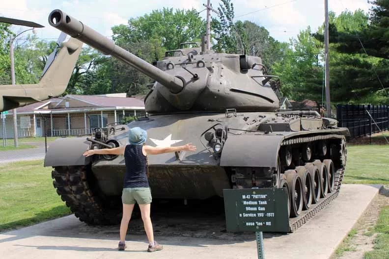 A woman standing in front of a tank with her arms out, mimicing Tank Man.