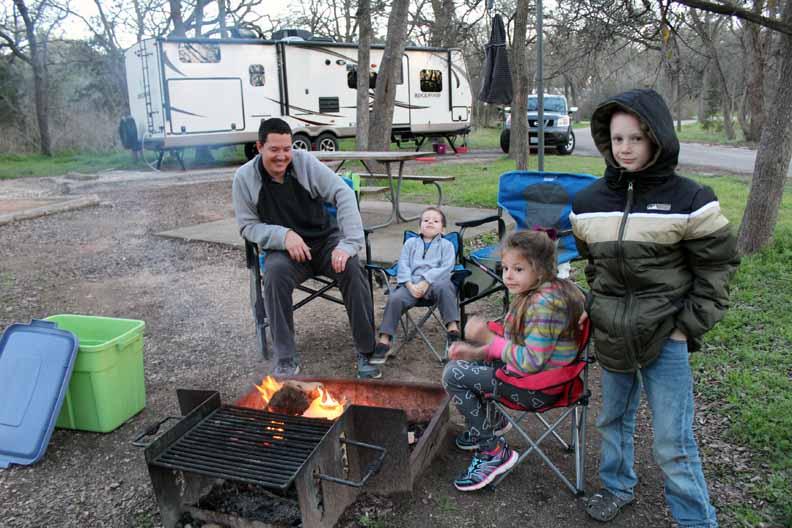 A family bonding around a camp fire.