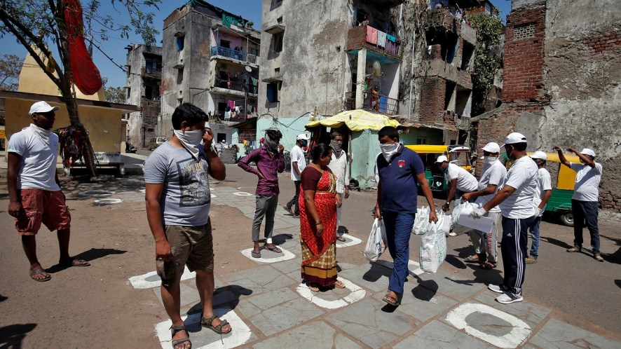Municipal workers distribute bags of food amongst the residents as they maintain safe distance during a 21-day nationwide lockdown to limit the spreading of coronavirus disease (COVID-19), in Ahmedabad, India, March 29, 2020. REUTERS/Amit Dave - RC2OTF94EPER