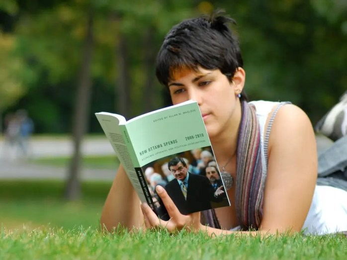 college student reading outside