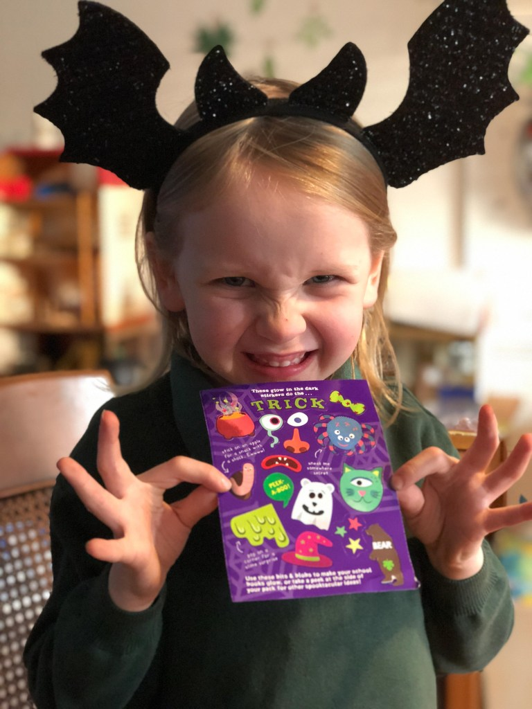 girl holding limited edition trick or treat stickers from BEAR Claws