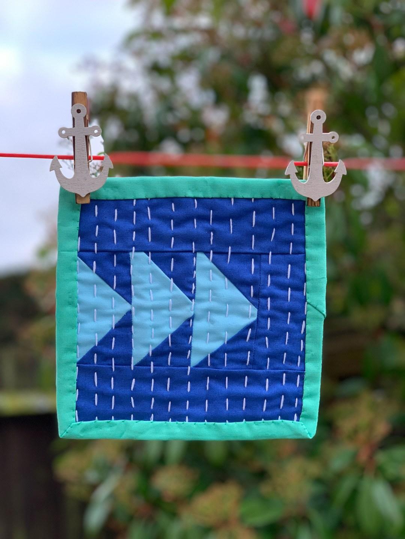 Moda Matchbox Mini quilt hanging on a washing line