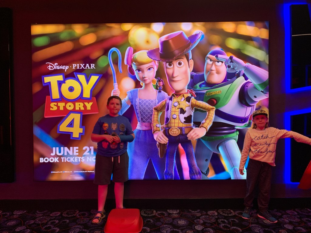 children standing in front of a Toy Story 4 poster