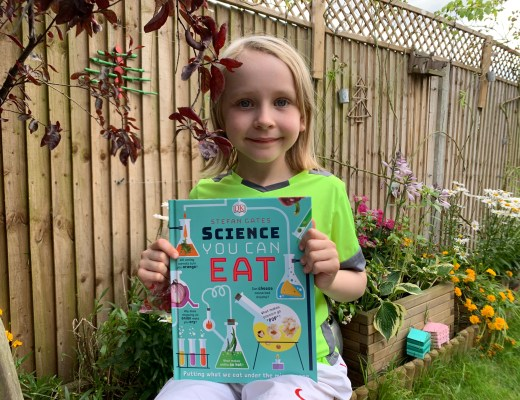 girl holding a copy of Science You Can Eat: Putting what we eat under the microscope