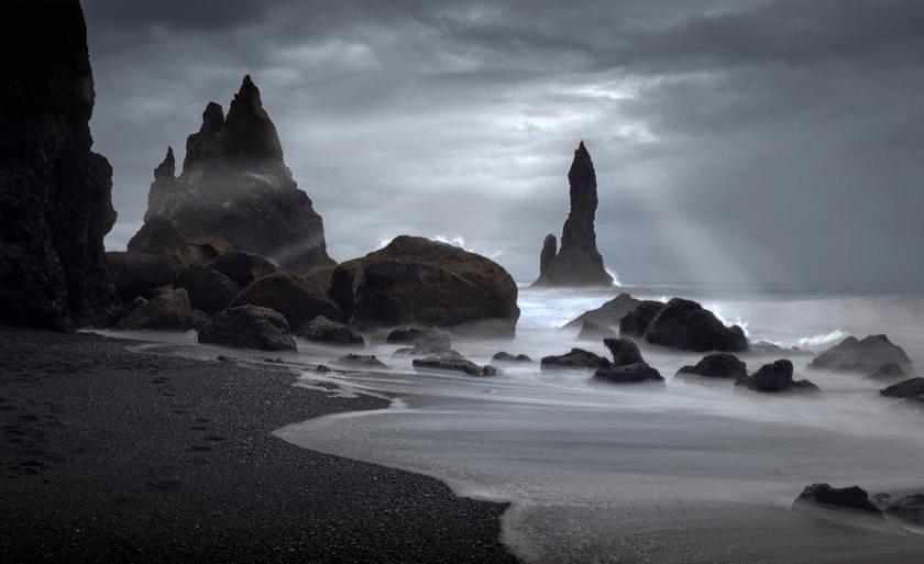 stormlucht en zonlicht op een humeurig rotsachtig strand