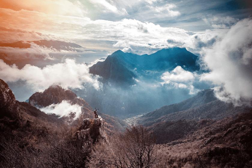 een persoon staat op een klif boven de bergen en de wolken