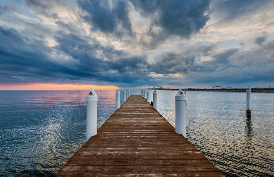 pijler die in het zeewater tijdens zonsondergang leidt