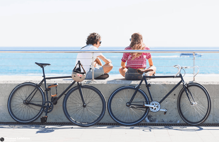twee meisjes zitten aan het strand met hun fietsen geparkeerd voor hun neus