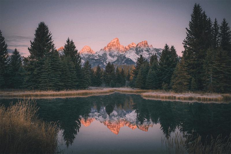 zonsondergang bergen en bomen weerspiegeld op een meer