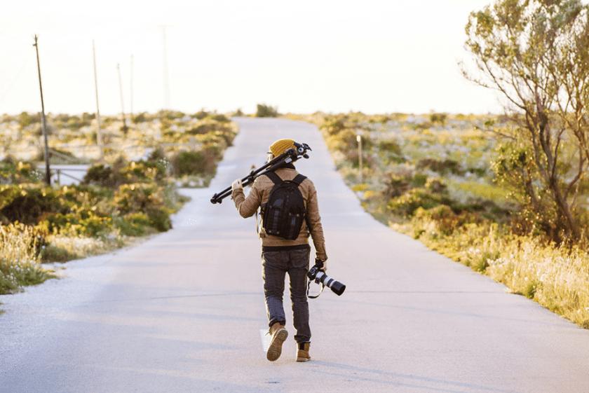 fotograaf lopen op een onverharde weg met een statief en camera