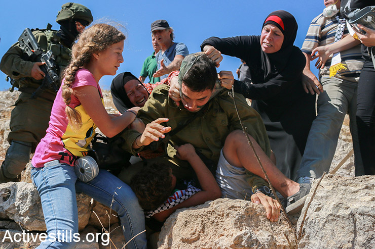 Members of the Tamimi family prevent an Israeli solider from arresting Mohammed Tamimi, 11, during the weekly protest against the occupation in the West Bank village of Nabi Saleh, August 28, 2015. (Activestills.org)