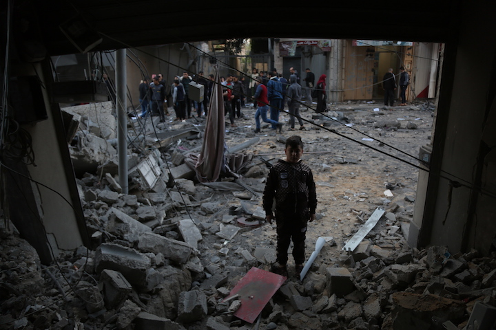 Palestinians in Gaza look on at the remains of the Yaziji building in Gaza City, following air strikes by the Israeli Air Force. Yaziji served as both a residential and commercial building, and was home to around 40 families, November 13, 2018. (Mohammad Zaanoun/Activestills.org)