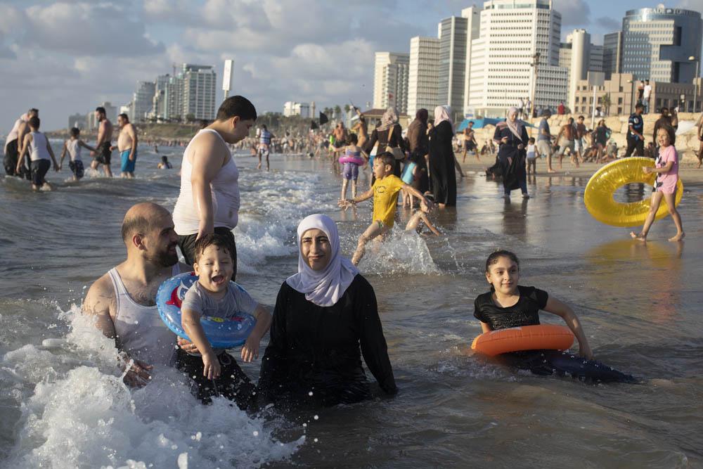 A Palestinian family enjoys the sea on the Jaffa beach. (Oren Ziv/Activestills)