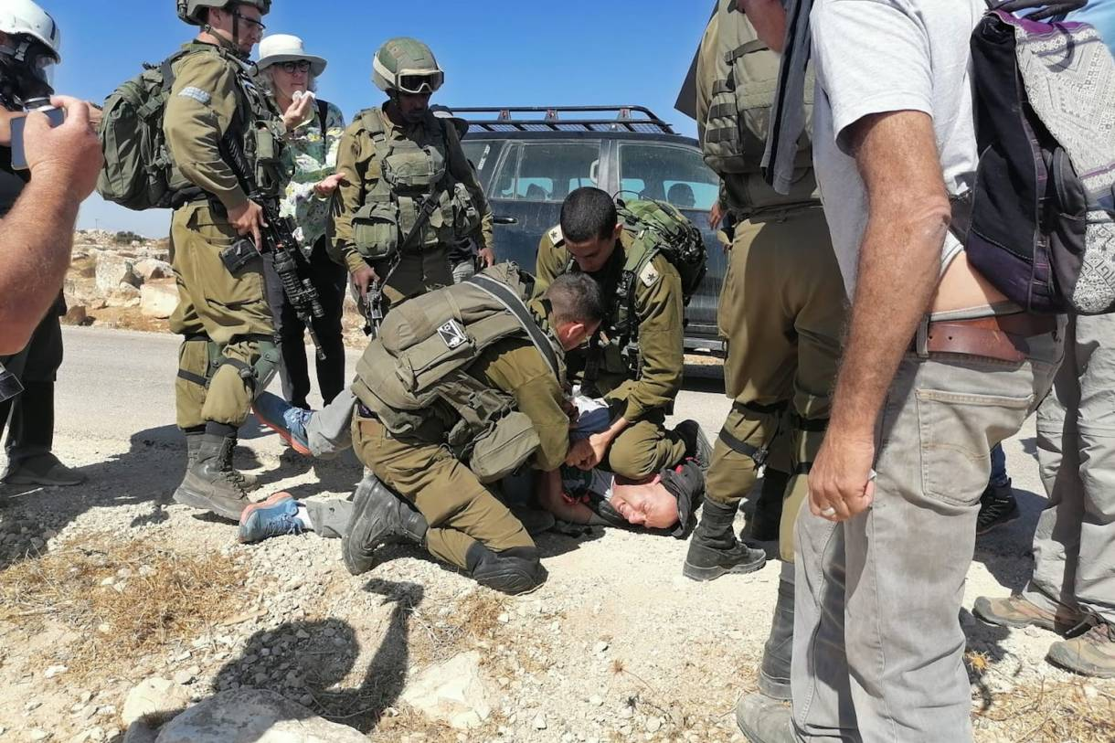 An Israeli soldier kneel on the neck of an Israeli left-wing activist during an attempt to bring water to Palestinian communities in the South Hebron Hills, April 17, 2021. (Osama Iliwat)