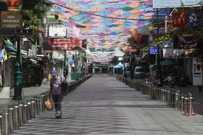 A man walks on a deserted street in the Khao San area on May 30, 2021, as the third wave has prompted strict Covid-19 control measures and brought activities in the popular tourism spot almost to a halt. (Photo: Apichit Jinakul)