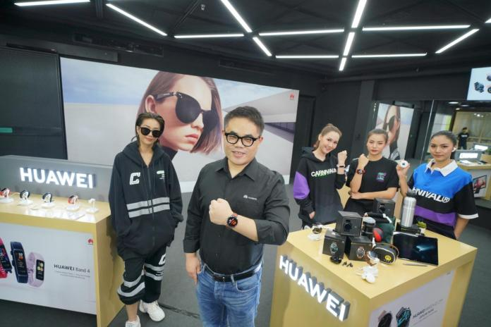 Mr Wang stands alongside presenters promoting gadgets at Huawei's launch event.