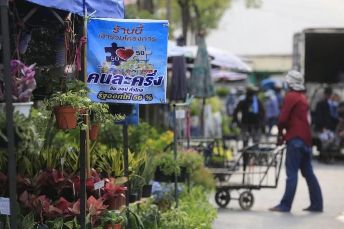 A sign is displayed in front of a shop participating in the Khon La Khrueng (half-half) co-payment scheme at Chatuchak weekend market.Pornprom Satrabhaya