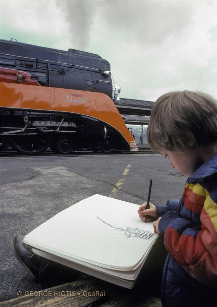 """""""In Portland, Oregon, a boy draws his favorite subject. He is totally absorbed and doesn't mind the camera. I squeezed behind him with a wide-angle lens to emphasize the foreground. The white paper acts as a fill-light reflector, and the soft light of a cloudy day is ideal for this situation."""" Photograph © George Hiotis"""