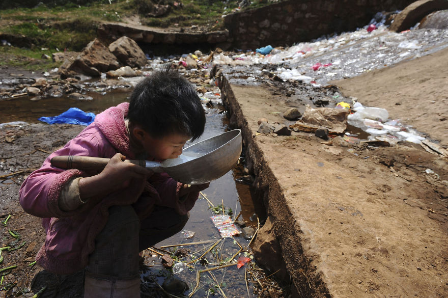 Child Drinks Water From Stream In Fuyuan County, Yunnan Province
