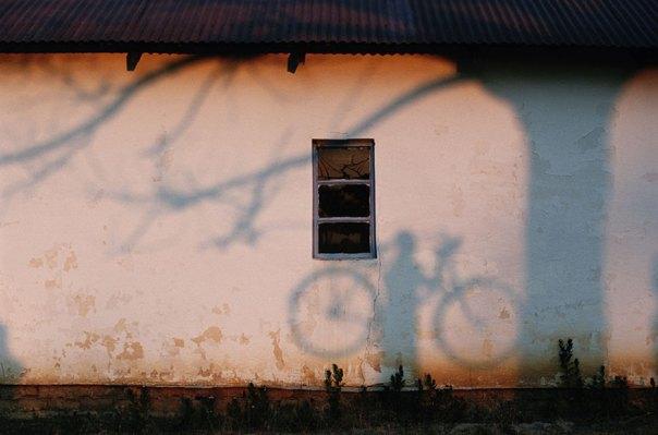A la sombra de un hombre con una bicicleta se proyecta sobre una pared cerca del río Zambezi, 1996