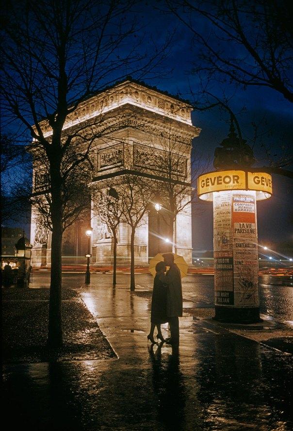 Los amantes jóvenes abrazo Al lado de El Arco del Triunfo en París, 1960