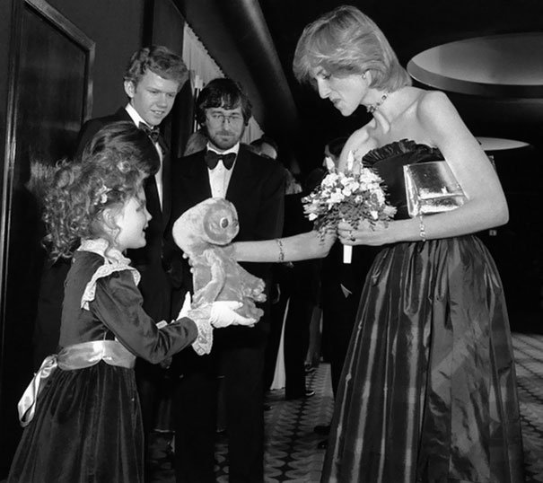 7-year-old Drew Barrymore giving Princess Diana an E.T. doll while Robert MacNaughton and Steven Spielberg is looking on at the London premiere of E.T.