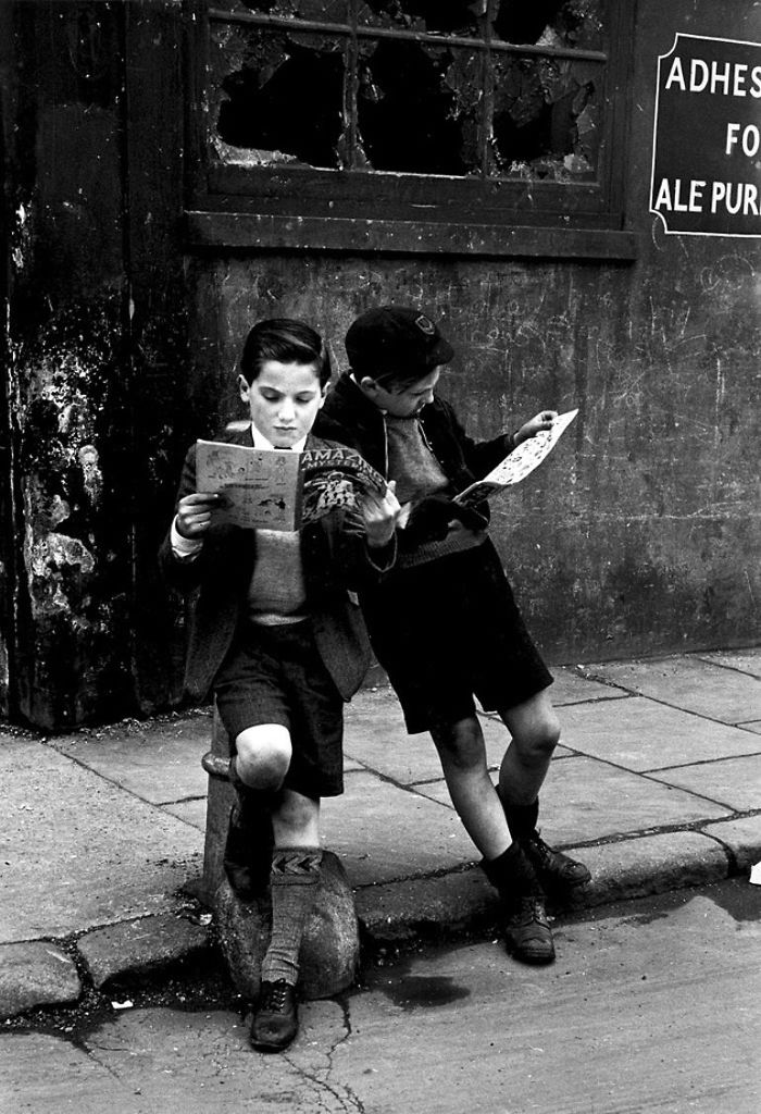 Two Boys Engrossed In Their Comic Books, Outside On The Street, 1952