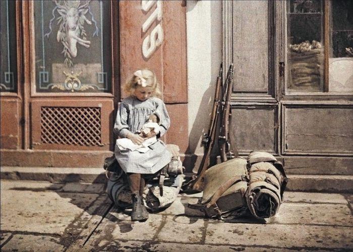 Uma menina segura uma boneca ao lado do equipamento de soldados em Reims, França, 1917