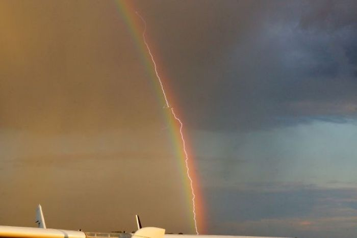 Lightning Strikes A Plane As It Flies Through A Rainbow