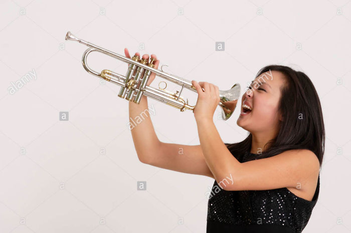 Stock Photograph Of A Pretty Asian Girl Screaming Into A Trumpet