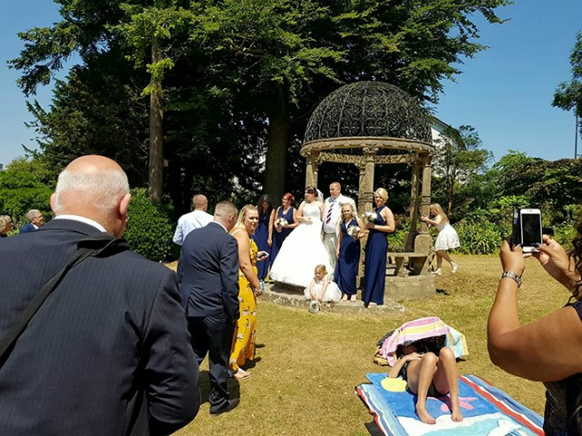 A wedding couple were left disgruntled when a shameless sunbather photobombed their wedding pictures by refusing to move. See story SWWEDDING. Newly-weds Mark Ling,49, and Mandy Cripwell, 35, were married in church on Saturday, and retired to a renowned beauty spot and public park to take what they hoped would be the perfect snaps. But their idyllic sun-kissed scene soon turned was ruined by a stubborn sunbather who had taken up residence on the green. The family of Torquay, Devon, say they asked the scantily-clad woman to move but she refused, and the wedding party were forced to pose for pictures around her. Mark's son, 24-year-old Marcus Ling, even approached the woman and asked her to move - but she pretended to be asleep.