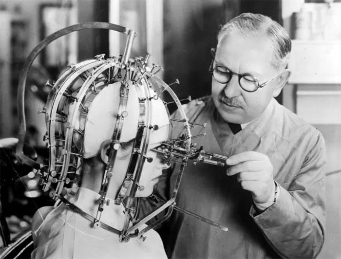 Fazendo medições precisas da cabeça e do rosto de uma bela jovem com uma engenhoca como um instrumento de tortura, 1933
