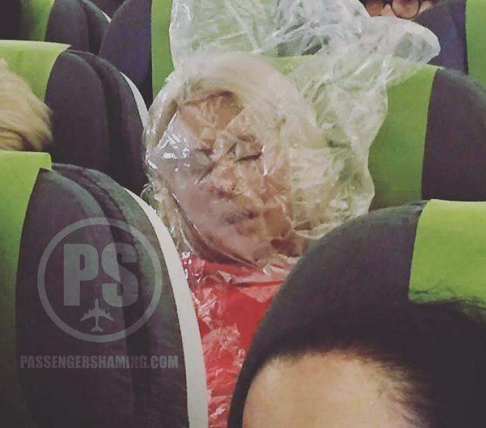 Esta pasajera del Premio Darwin estaba fría ... así que usó la bolsa de plástico (que tenía una manta / almohada) y la puso sobre su cabeza Para calentar