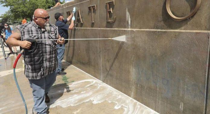 Добровольцы убирают граффити на строительстве Капитолия в штате Юта.
