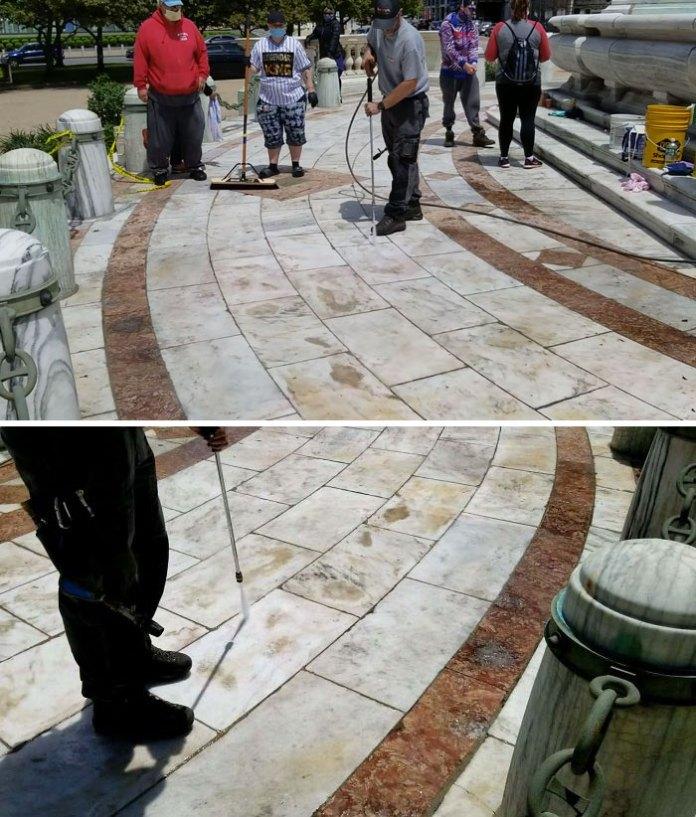 Спрей протестующих нарисован по всему этому памятнику прошлой ночью.  Мы все пытались очистить его, когда этот парень появился с Powerwasher.